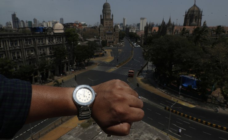 A photographer wearing a watch at noon shows the time while taking a photo of almost empty roads outside the Chhatrapati Shivaji Maharaj Terminus, during the coronavirus disease (COVID-19) outbreak, in Mumbai, India, March 31, 2020. Reuters