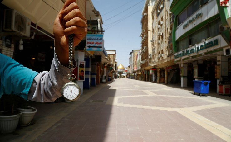 A man holds a pocket watch at noon, as he shows the time while posing for photo at an almost empty market near the Imam Ali shrine, during the coronavirus disease (COVID-19) outbreak, in Najaf, Iraq, March 31, 2020. Reuters