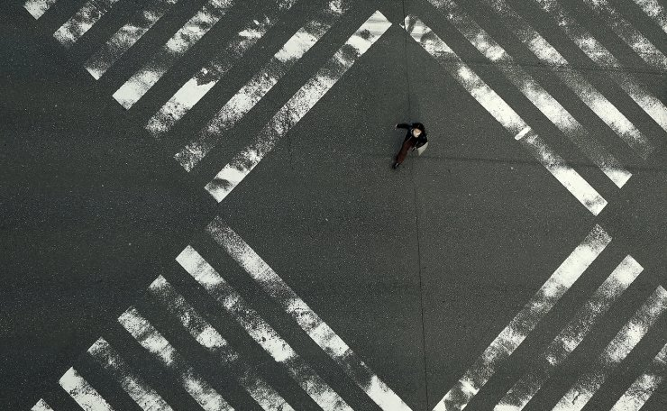 A woman walks through an empty pedestrian crossing in the Ginza shopping district Friday, April 3, 2020, in Tokyo. The new coronavirus causes mild or moderate symptoms for most people, but for some, especially older adults and people with existing health problems, it can cause more severe illness or death. AP
