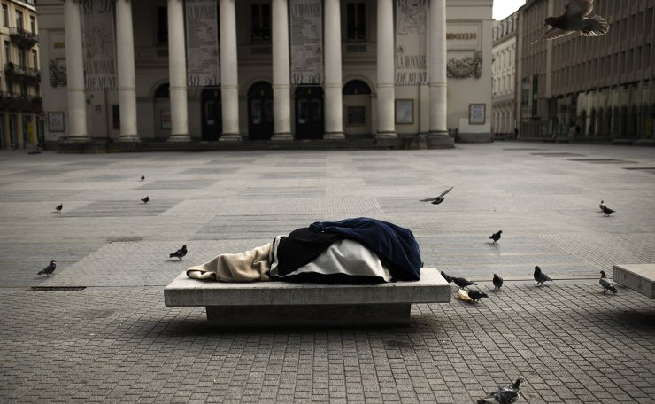 A homeless person sleeps on a bench in the virtually empty La Monnaie square during a partial lockdown against the spread of the Covid-19 coronavirus in Brussels, Friday, April 3, 2020. AP