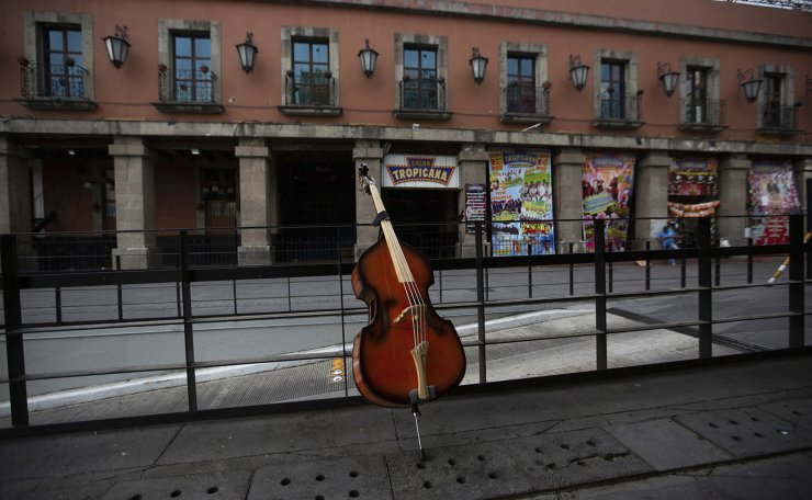 A double bass leans against a barrier in the popular Garibaldi square, now empty of visitors in Mexico City, Friday, April 3, 2020. AP