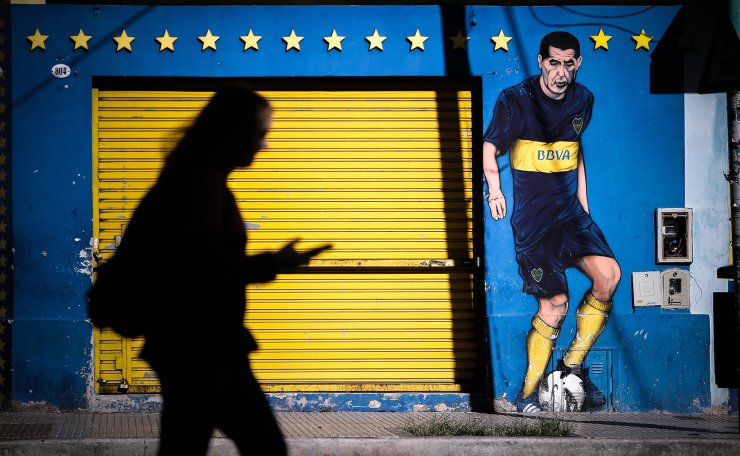 Silhouette of a woman walking by a graffiti of soccer player Juan Roman Riquelme, in the neighborhood of La Boca, after more than 25 days since soccer tournaments were stopped as a result of the COVID-19, in Buenos Aires, Argentina, 06 April 2020. EPA