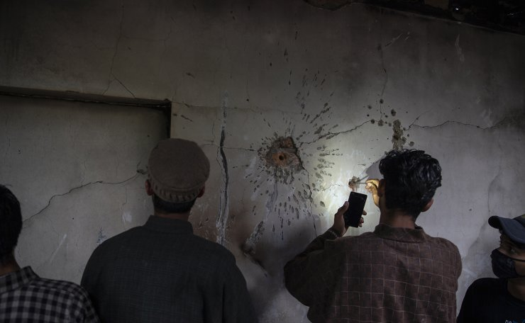 A Kashmiri boy tries to take out a bullet from the wall of a damaged house after a gunbattle in Tral, south of Srinagar, Indian controlled Kashmir, May 24, 2019. AP