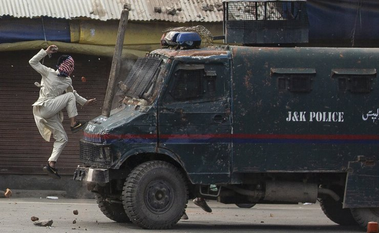 A masked Kashmiri protester jumps on the bonnet of an armored vehicle of Indian police as he throws stones at it during a protest in Srinagar, Indian controlled Kashmir, May 31, 2019. AP