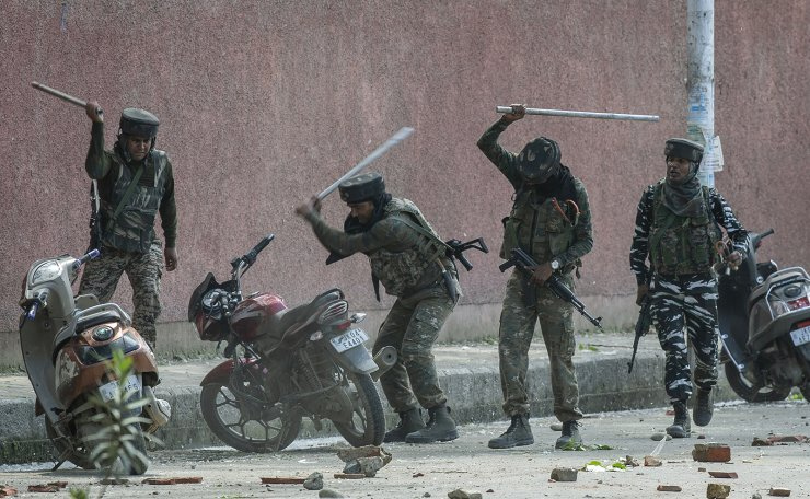 Indian paramilitary soldiers break motorbikes parked outside a college as they clash with students protesting against the alleged rape of a 3-year-old girl in Srinagar, Indian controlled Kashmir, May 14, 2019. AP