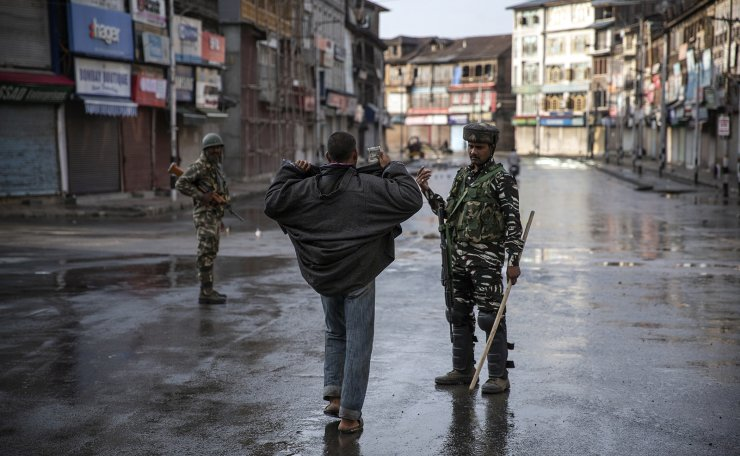An Indian paramilitary soldier orders a Kashmiri to open his jacket before frisking him during curfew in Srinagar, Indian controlled Kashmir, Aug. 8, 2019. AP