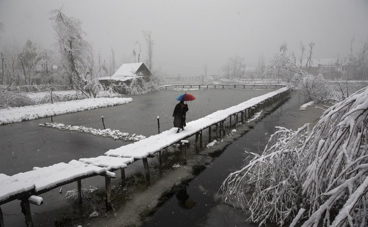 A Kashmiri man walks on a snow covered footbridge as it snows in the interiors of Dal Lake in Srinagar, Indian controlled Kashmir, Dec. 13, 2019. AP