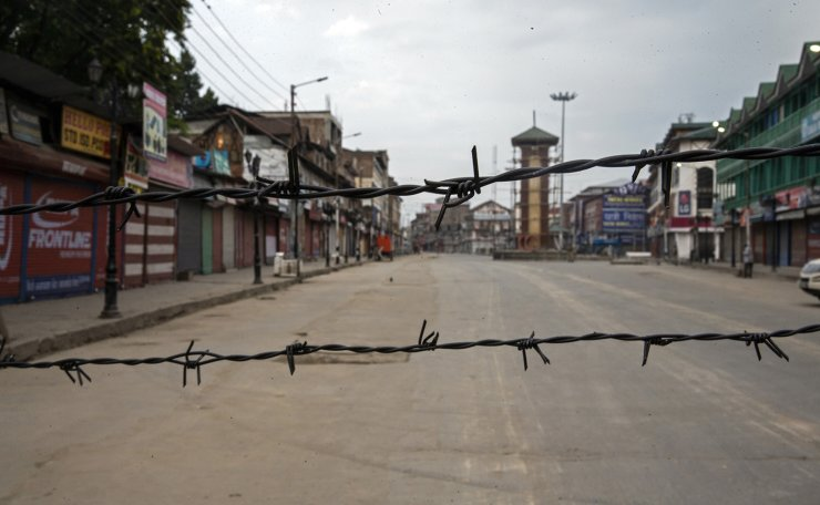 A deserted street is seen through barbwire set up as a blockade during curfew in Srinagar, Indian controlled Kashmir, Aug. 6, 2019. AP