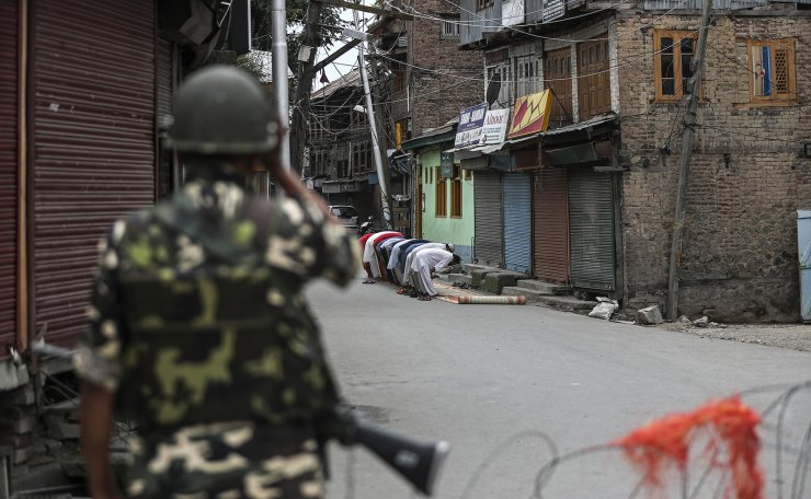 An Indian paramilitary soldier stands guard as Kashmiri Muslims offer Friday prayers on a street outside a local mosque during curfew like restrictions in Srinagar, India, Aug. 16, 2019. AP
