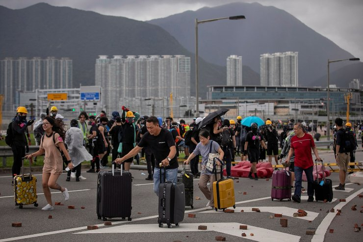Passengers push their luggage past bricks and barriers after anti-government protesters blocked the roads leading to Hong Kong International Airport, in Hong Kong, China, September 1, 2019. REUTERS