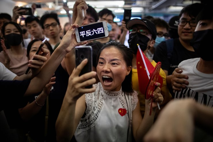 A pro-China demonstrator films herself as an anti-government protester holds up a sign on her phone during skirmishes between the two opposing groups at Yuen Long station in Hong Kong, China, September 12, 2019. The words on the phone read, 'Seek an official reassessment of the June 4 crackdown,' referring to the 1989 Tiananmen Square protests. REUTERS
