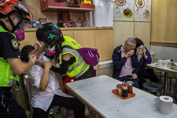 A restaurant worker receives help from volunteers as patrons cover their faces after riot police fired tear gas nearby to disperse anti-government protesters taking part in a march billed as a global 'emergency call' for autonomy, in Hong Kong, China November 2, 2019. REUTERS