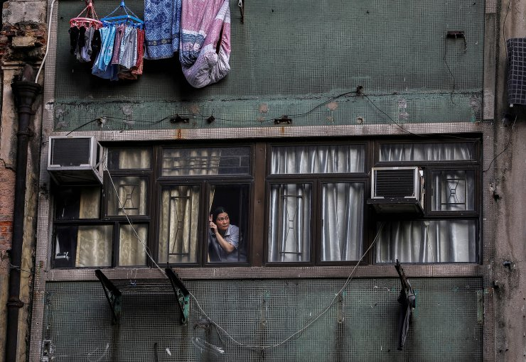 A woman looks out from the window of a residence as tens of thousands of demonstrators march through Hong Kong, China on October 20, 2019, demanding autonomy and for its leaders to step down weeks after the formal withdrawal of an extradition bill. The protests where triggered in February 2019 after Hong Kong?s Security Bureau proposed amendments to extradition laws that would allow extraditions to countries, including mainland China, beyond the 20 states with which Hong Kong already has treaties. REUTERS