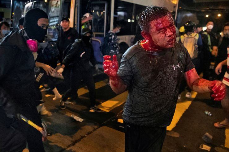 A masked anti-government protester, wielding a hammer, attacks a man who bystanders suspected of being a pro-Beijing activist from mainland China, during a protest in the Mong Kok area in Hong Kong, China November 11, 2019. The bloodied man, who suffered major facial and head trauma, was reported to have survived his injuries by local media. REUTERS