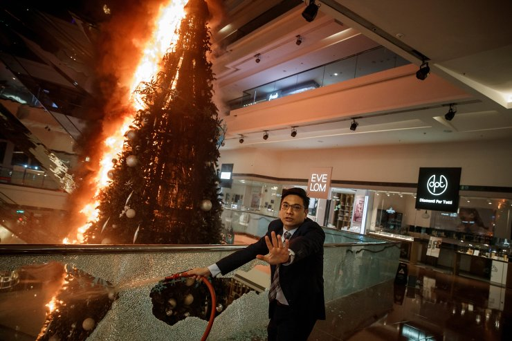 Mall security personnel urges caution as he tries to extinguish a burning Christmas tree at the Festival Walk mall in Kowloon Tong, Hong Kong, China November 12, 2019. REUTERS