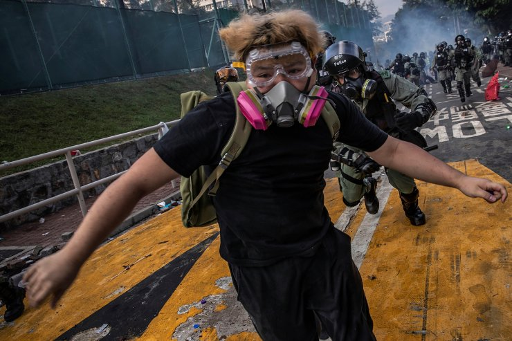 An anti-government protester, who later identified himself as a university student, is chased by riot policemen after skirmishes at the Chinese University of Hong Kong, in Hong Kong, China November 12, 2019. REUTERS