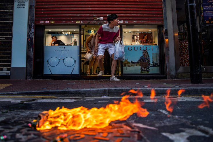 Customers cautiously exit an eyeglass store past a burning molotov cocktail as demonstrators clash with riot policemen  during a march billed as a global 'emergency call' for autonomy, in Hong Kong, China November 2, 2019. REUTERS