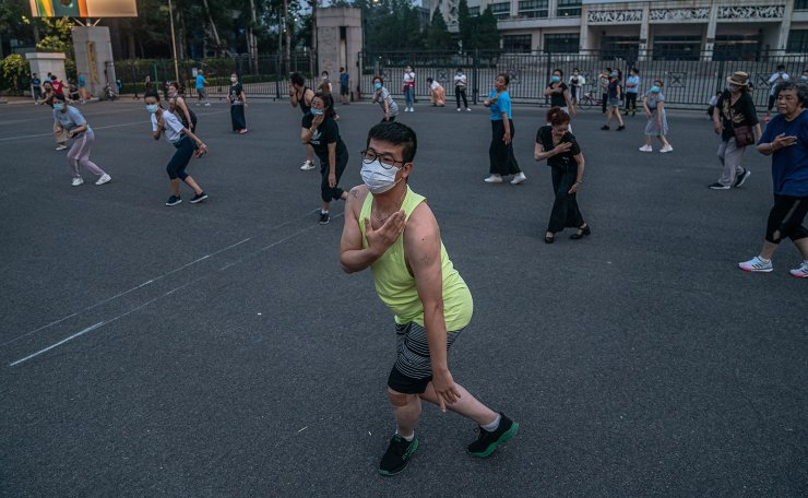 People wearing protective face masks dance in the street amid coronavirus pandemic in Beijing, China, 27 June 2020. Beijing is currently imposing strict safety measures to halt the spread of new coronavirus outbreak in the city. EPA