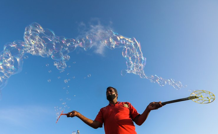 A street artist wears a face mask while creating soap bubbles at the Galle Face promenade in Colombo, Sri Lanka, 27 June 2020. The Sri Lankan government has started lifting most of the restrictions implemented nearly four months ago in a bid to slow down the spread of the SARS-CoV-2 coronavirus that causes the COVID-19 disease, and is preparing for a full reopening of businesses and activities to avoid an economic slump.  EPA