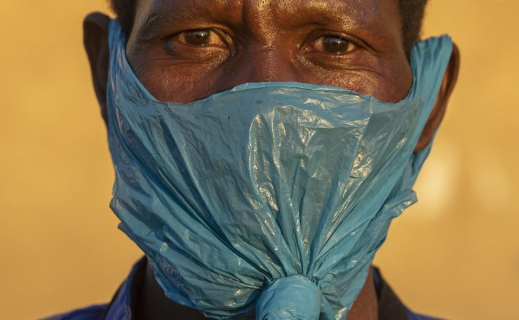 In this May 6, 2020 file photo a man wears a plastic bag for a mask on his face as a precaution against the spread of the coronavirus, in Katlehong, Johannesburg.  AP