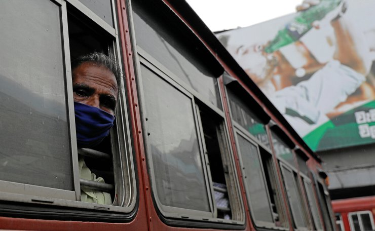 A passenger wearing a protective mask looks out from the window of a bus at a main bus station, amid concerns about the spread of the coronavirus disease (COVID-19), in Colombo, Sri Lanka, June 29, 2020. Reuters