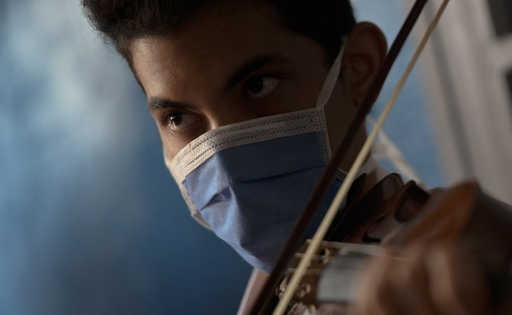 A man wearing a mask due to the new coronavirus pandemic plays his violin during a ceremony marking 101 years since the death of Venezuelan Dr. Jose Gregorio Hernandez in La Pastora neighborhood of Caracas, Venezuela, Monday, June 29, 2020. Pope Francis approved on Friday, June 19, 2020, the beatification of Hernandez, known as the 'doctor of the poor.' AP