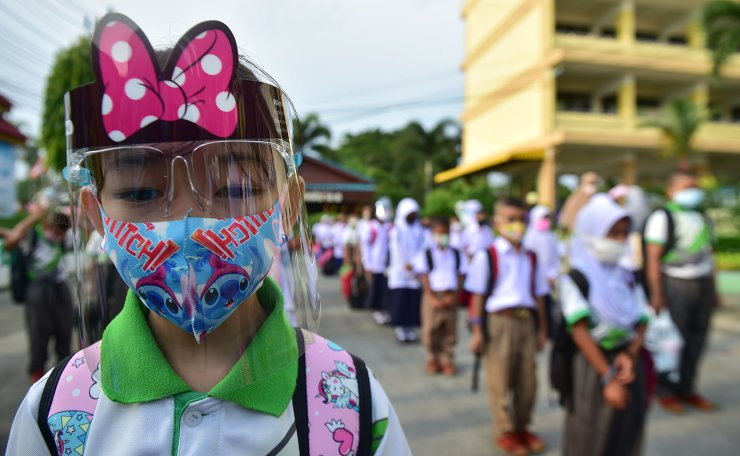 A student wears a face shield while observing social distancing as they line up to attend classes in a school in the southern Thai province of Narathiwat on July 1, 2020, as schools reopened after being temporarily closed due to the threat of the COVID-19 novel coronavirus. AFP