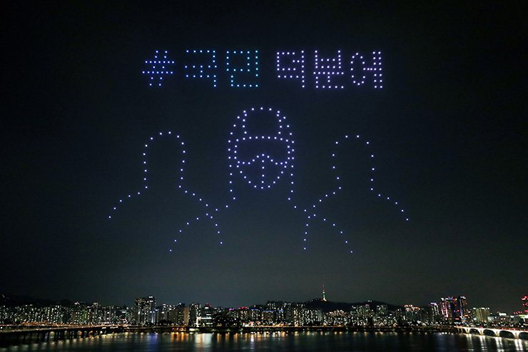 In this on Saturday, July 4, 2020, photo, some 400 drones fly over the Han River showing messages of appreciation for medical workers during the coronavirus pandemic in Seoul, South Korea. The letters read ' Thanks to the people.' AP-Yonhap