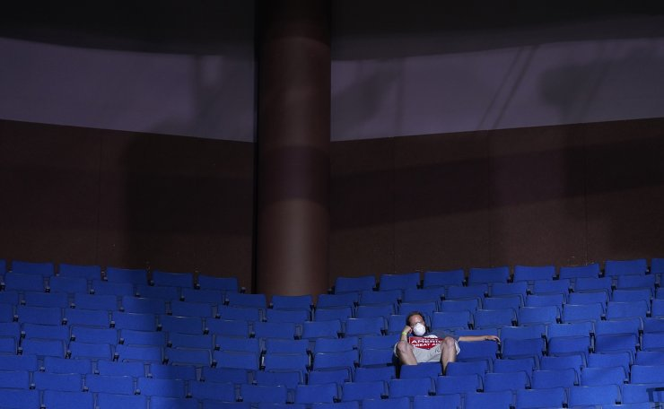 In this June 20, 2020, file photo, a supporter of President Donald Trump sits in the stands wearing a face mask during a campaign rally at the BOK Center in Tulsa, Okla. AP