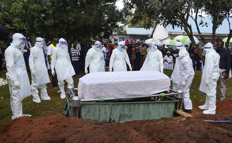 Health officials wearing personal protection equipment prepare to bury coronavirus victim Dr. Doreen Adisa Lugaliki at her burial in Ndalu, Bungoma county, Kenya Monday, July 13, 2020. AP