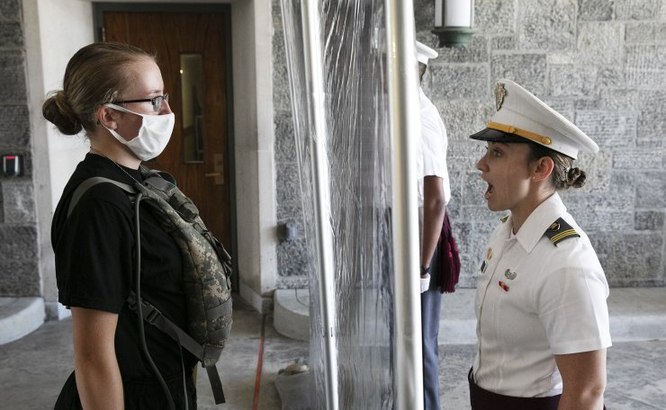 A new cadet, left, listens as First Class Cadet Madison Teague, right, yells commands as a plastic screen separates them at the U.S. Military Academy, Monday, July 13, 2020, in West Point, N.Y. The Army is welcoming more than 1,200 candidates from every state. Candidates will be COVID-19 tested immediately upon arrival, wear masks, and practice social distancing. AP