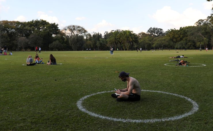 A man sits in a field where circles were painted to help visitors maintain social distancing at Ibirapuera Park after it was reopened as the city eases the restrictions imposed to control the spread of the coronavirus disease (COVID-19), in Sao Paulo, Brazil July 13, 2020. Reuters