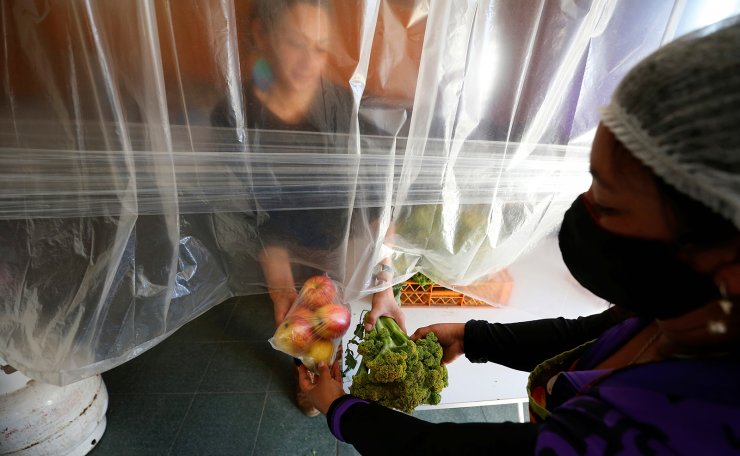 A volunteer delivers food rations at a so-called 'Olla comun', a communal kitchen set up to provide hot food for those with dwindling incomes or nothing, on a hill named 'Mariposas' (butterflies), during the spread of the coronavirus disease (COVID-19), in Valparaiso, Chile  July 13, 2020. Reuters