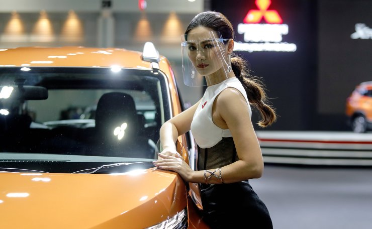 A model wearing a face shield poses with a Mitsubishi vehicle during the media day of the 41st Bangkok International Motor Show after the Thai government eased measures to prevent the spread of the coronavirus disease (COVID-19) in Bangkok, Thailand July 14, 2020. Reuters