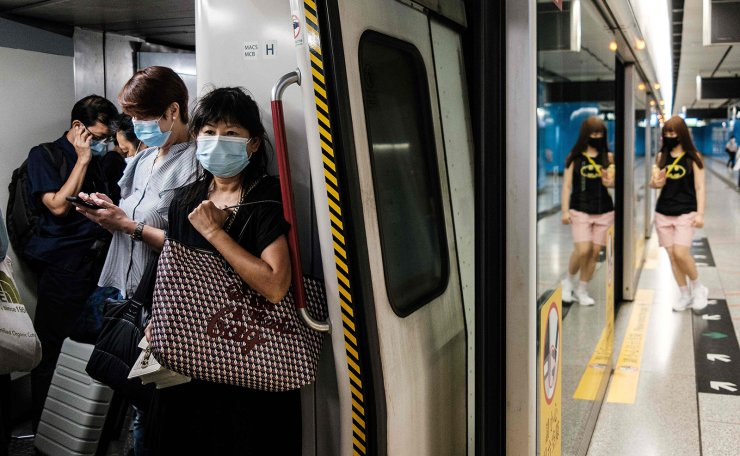 Commuters wear face masks on a metro train in Hong Kong on July 15, 2020, as the city experiences a spike in COVID-19 coronavirus cases. AFP