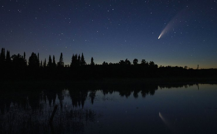 Comet Neowise streaks across the night sky over Wolf Lake in Brimson, Minn., Tuesday night, July 14, 2020. Comet C/2020 F3 Neowise is a bright comet that only passes close enough for viewing on Earth once every 6,800 years or so. AP