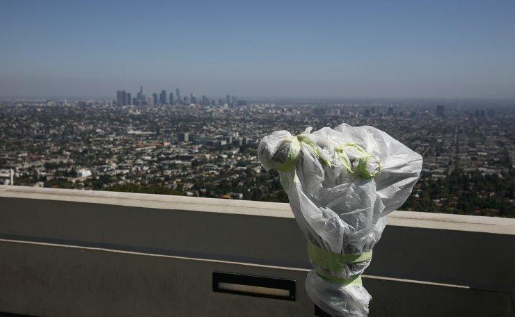 A telescope is seen wrapped in plastic to prevent the spread of COVID-19 at the Griffith Observatory overlooking downtown Los Angeles, Wednesday, July 15, 2020. AP