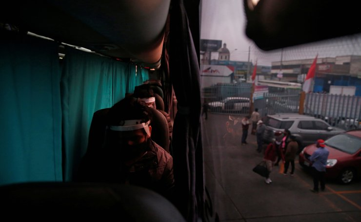 Passengers sit, separated by a curtain from their neighbours, on a bus during the outbreak of the coronavirus disease (COVID-19), in Lima, Peru July 15, 2020. Reuters