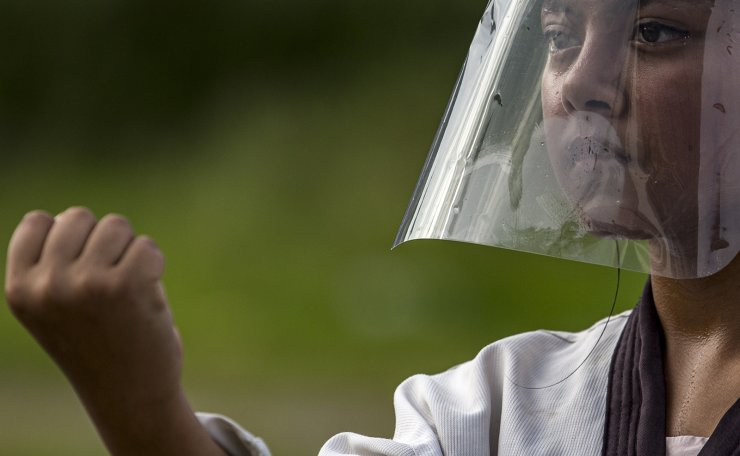 A Nepalese student wears a face shield at a training class during a partial lockdown for the coronavirus pandemic in Kathmandu, Nepal, 16 July 2020. The Lainchour Takenwondo Dojang has resumed self-defense martial art classes for people aged between seven and 18-years-old at a community ground in Kathmandu. The Nepal government has started to ease the COVID-19 lockdown in an effort to restart its economy. EPA
