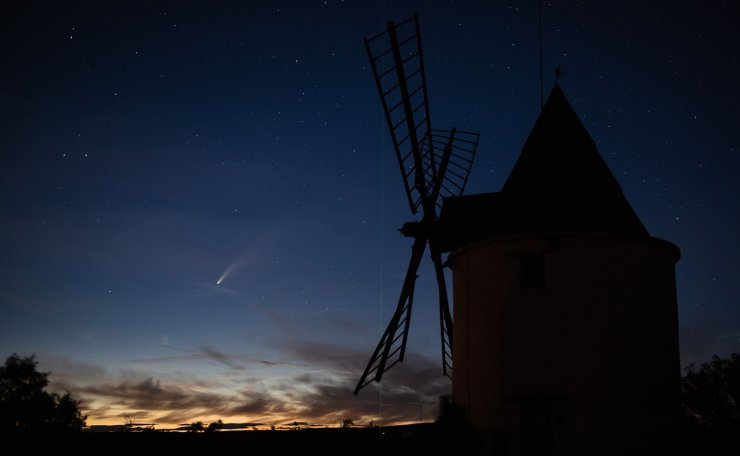 A picture taken on July 15, 2020 shows the C/2020 F3 comet (L), also known as 'NEOWISE', and the green laser beam used by the Haute-Provence Observatory to point celestial objects for studies and researches (C), with an old windmill in the foreground in Saint-Michel-L'Observatoire, southern France. AF[