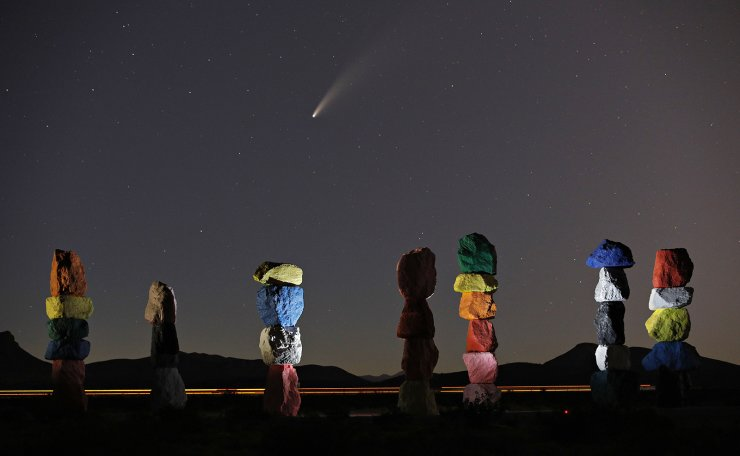 The comet Neowise, or C/2020 F3, is seen in the evening sky above the artwork titled: 'Seven Magic Mountains' by artist Ugo Rondinone, Thursday, July 16, 2020, near Jean, Nev., south of Las Vegas. AP