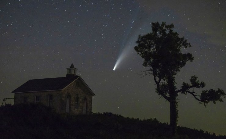 The comet Neowise can be seen from a 19th century one-room schoolhouse at the Tallgrass National Prairie Preserve near Strong City, Arc., Friday night, July 17, 2020. The comet will still be visible in the northwest sky for the next few nights. AP