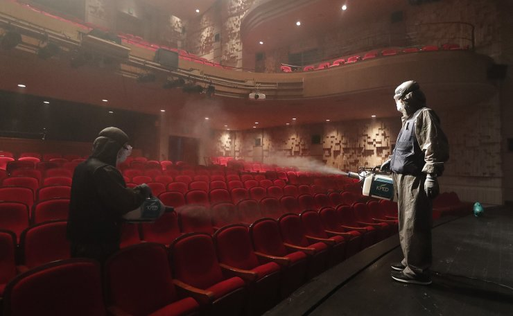 Workers wearing protective gears spray disinfectant as a precaution against a new coronavirus at a theater in Sejong Center in Seoul, South Korea, Tuesday, July 21, 2020. South Korea's new virus cases have bounced back Tuesday, a day after it reported its smallest daily jump in local COVID-19 transmissions in two months. AP