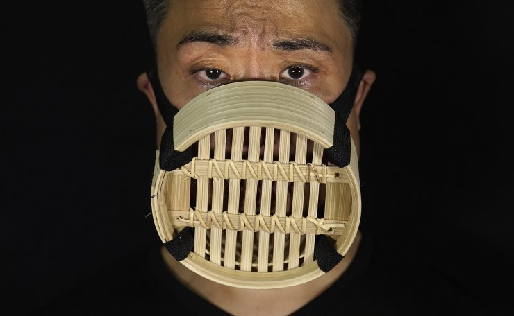 Edmond Kok, a Hong Kong theater costume designer and actor, wearing a face mask made from Chinese bamboo steamer in Hong Kong Thursday, Aug. 6, 2020. AP