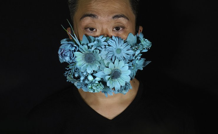 Edmond Kok, a Hong Kong theater costume designer and actor, wearing a face mask covered in blue artificial flowers which he made on Valentine's Day this February in Hong Kong Thursday, Aug. 6, 2020. AP