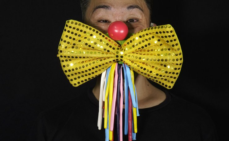 Edmond Kok, a Hong Kong theater costume designer and actor, wearing a face mask designed as traditional clown face and bow tie costume in Hong Kong Thursday, Aug. 6, 2020. AP