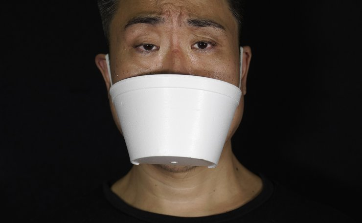 Edmond Kok, a Hong Kong theater costume designer and actor, wearing a face mask made from takeaway container in Hong Kong Thursday, Aug. 6, 2020. AP