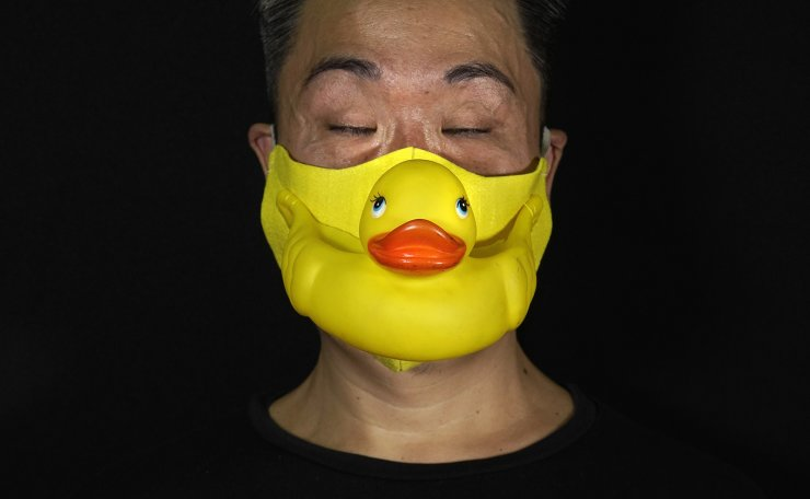 Edmond Kok, a Hong Kong theater costume designer and actor, wearing a face mask made by a rubber yellow duck in Hong Kong Thursday, Aug. 6, 2020. AP