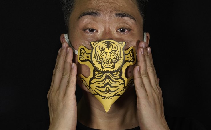 Edmond Kok, a Hong Kong theater costume designer and actor, wearing a face mask made by a paper tiger use for villain hitting in Hong Kong Thursday, Aug. 6, 2020. AP