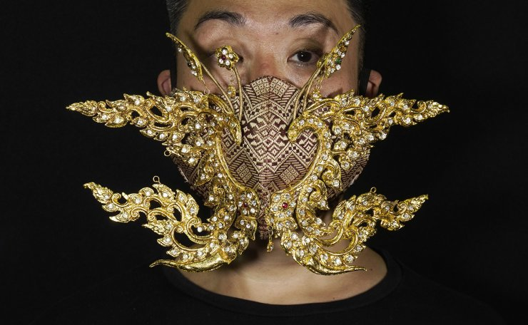 Edmond Kok, a Hong Kong theater costume designer and actor, wearing a face mask inspired by the decoration of Thai temple to Kok's face in Hong Kong Thursday, Aug. 6, 2020. AP